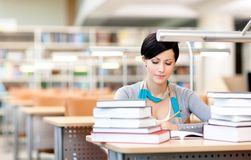 Young female studies with piles of books Royalty Free Stock Image