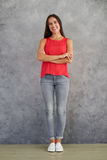 Young female in stylish casual wear standing against gray backgr Stock Photography
