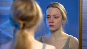 Young female suffering depression, crying looking at mirror reflection, despair