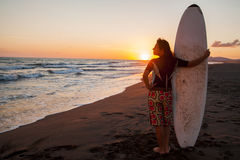 Young female surfer on beach in sunset. Young female surfer holding board on sandy beach in sunset Royalty Free Stock Photo