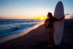 Young female surfer on beach in sunset Stock Photo