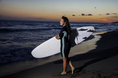 Young female surfer on beach in sunset. Young female surfer holding board on sandy beach in sunset Royalty Free Stock Photography