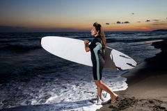 Young female surfer on beach in sunset. Young female surfer holding board on sandy beach in sunset Stock Images