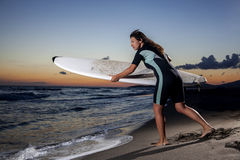 Young female surfer on beach in sunset. Young female surfer holding board on sandy beach in sunset Stock Photo