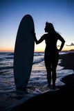Young female surfer on beach in sunset. Silhouette of young female surfer holding board on sandy beach in sunset Royalty Free Stock Photos