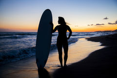 Young female surfer on beach in sunset. Silhouette of young female surfer holding board on sandy beach in sunset Stock Image