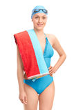Young female swimmer in a blue swimsuit. Carrying a towel over her shoulder and looking at the camera isolated on white background royalty free stock photos