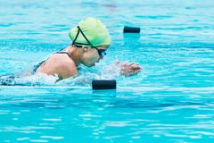 Young female swimmer races in breath stroke and raises up to cat Royalty Free Stock Images