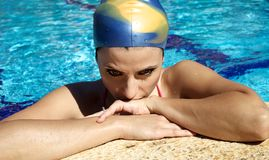 Young female swimmer thinking about competition in swimming pool for world record. Beautiful woman professional swimmer ready for competition Stock Photos