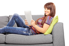 Young female with tablet computer or electronic book on sofa Royalty Free Stock Photography