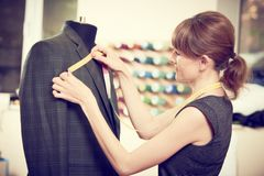 Female tailor works with male suit. Young female tailor works with male suit in workshop Stock Photo