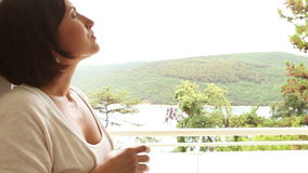 Young female takes a deep breath on the resort hotel  balcony. 