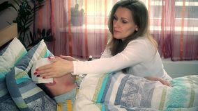 Young female taking care of her sick husband man in bed stock video footage
