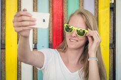 Young female taking selfie in front of colorful wooden wall stock photos
