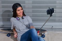 Young female taking selfie. Young female with headphones taking selfie while laying back on skateboard Stock Photography