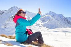 Young female taking a selfie on her phone on a beautiful mountain top. Winter time royalty free stock images