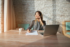 Young female talking on a cell phone. Beautiful young Asian talking on a cell phone while writing pen on a paper document while sitting in an expensive Royalty Free Stock Images