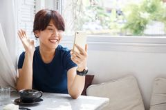 Young female talking with her friend on smartphone device. Copy stock photo