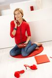 Young female talking on phone in red pullover Stock Images