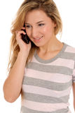 Young female talking by telephone and smiling Royalty Free Stock Images