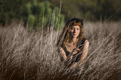 Young female in tall dry hay grass Royalty Free Stock Image