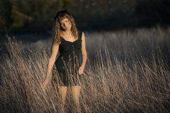 Young female in tall dry hay grass Royalty Free Stock Images