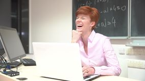 Young female teacher browsing files while sitting at desk with laptop in modern classroom stock video