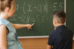 Young female teacher help schoolboy. Boy stand by the blackboard.  royalty free stock photo