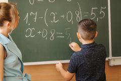 Young female teacher help schoolboy. Boy stand by the blackboard.  stock photo