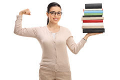 Young female teacher holding stack of books and flexing biceps royalty free stock photography