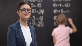 Young female teacher looking to camera, schoolboy solving math exercises, job. Stock footage stock footage