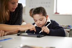 Young female teacher working with a Down syndrome schoolboy sitting at desk using a tablet computer in a primary school classroom, stock photo