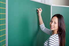 Young female teacher writing on blackboard Stock Image