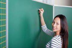 Young female teacher writing on blackboard Stock Image