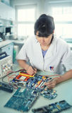 Young female tech or engineer repairs electronic equipment in re Stock Image