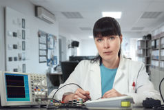Young female tech or engineer repairs electronic equipment Royalty Free Stock Photography