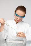 Young female tech or scientist loads sample Stock Photos