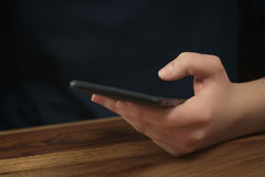 Young female teen hand using smatphone sitting at the table closeup Stock Photos