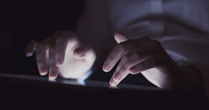 Young female teen using tablet pc in the dark environment very shallow focus Stock Image