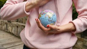 Young female teenager in pink casual clothes with red manicure holding a little globe with geografical names in. Ukrainian cyrillic letters on it in her hands stock video