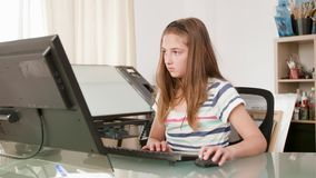 Young female teenager working on a computer and types a text. Teenager girl busy doing her homework stock video
