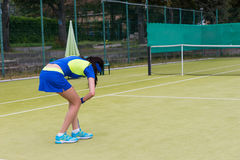 Young female tennis player bent down for a ball Royalty Free Stock Images