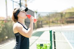 Female tennis player having energy drink. Young female tennis player drinking red liquid energy drink during practising on outdoor tennis court Stock Images