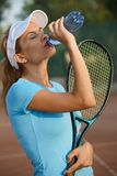Young female tennis player drinking water royalty free stock image
