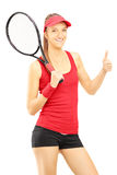 Young female tennis player giving thumb up Stock Photo