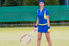 Young female tennis player holding a racket and a ball on tennis Stock Images