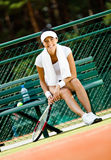 Young female tennis player rests at the bench Royalty Free Stock Photo