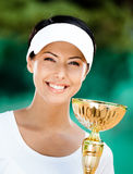 Young female tennis player won the competition. Professional female tennis player won the cup at the sport competition. Prize Royalty Free Stock Photo