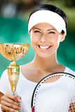 Young female tennis player won the cup. Tennis player won the cup at the sport match. Trophy Stock Images