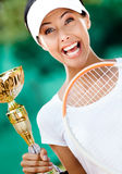 Young female tennis player won the match. Tennis player won the cup at the sport tournament. Trophy Royalty Free Stock Photo